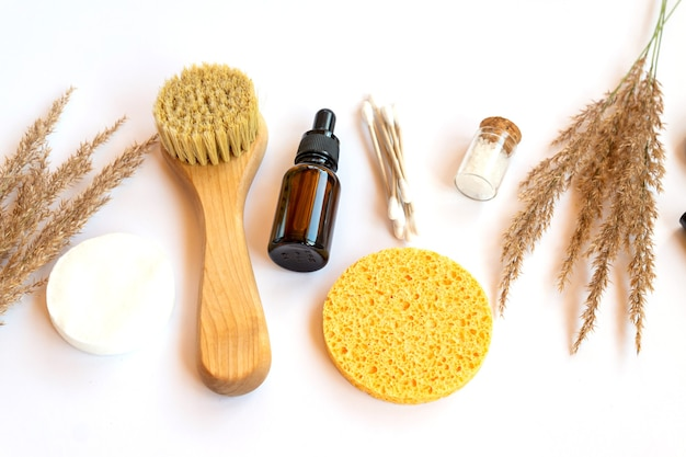Spa and wellness concept with sea salt, dry pampas, brush, oil and face sponges on white background, top view