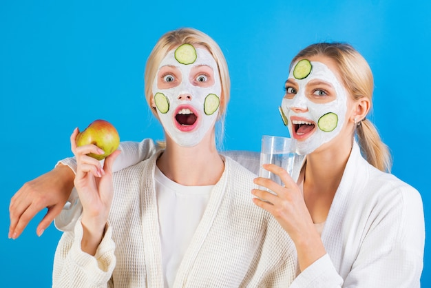 Spa and wellness. girls friends sisters making clay facial mask. anti age mask. stay beautiful. skin care for all ages. women having fun cucumber skin mask. drink water eat fruits. health concept.