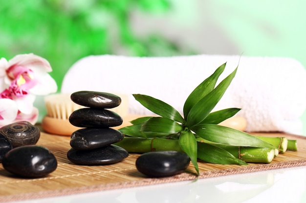 Spa and wellness, massage stones and flowers on wooden tablecloth