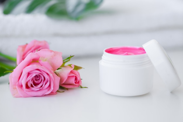 Spa. wellness products and cosmetics. towels, cream and pink flowers for a spa relaxation. natural organic cosmetics for face care. bath products, bathroom set