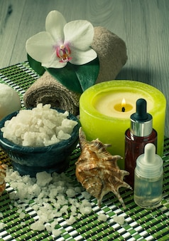 Spa and wellness setting with orchid flower, bowl with sea salt, seashells, bottles with aromatic oil, candle and towel on bamboo napkin and wooden background