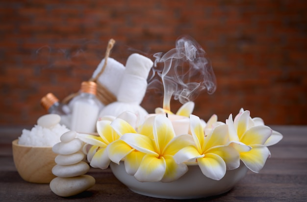 Spa wellness and treatment with essential oils,zen stone,towels,candle,hearbal massage ball and frangipani flowers on wooden table with brick wall