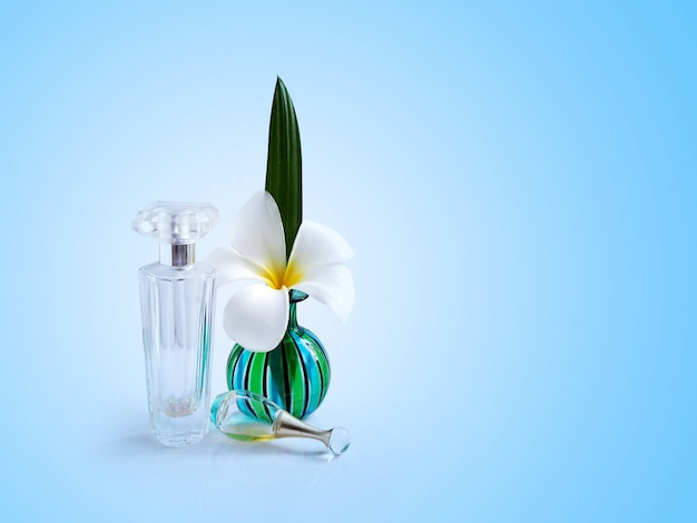 Spa white plumeria flowers in green vase with clear glass perfume bottle