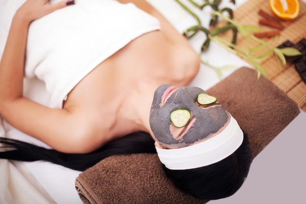 Женщина спа, применяющая очищающую маску для лица