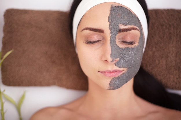 Spa woman applying facial cleansing mask.