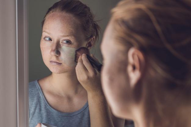 フェイシャルグリーンクレイマスクを適用するスパの女性。美容トリートメント。顔のマスクを適用する美しい少女のクローズアップの肖像画