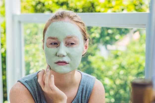 스파 여자 얼굴 녹색 클레이 마스크를 적용