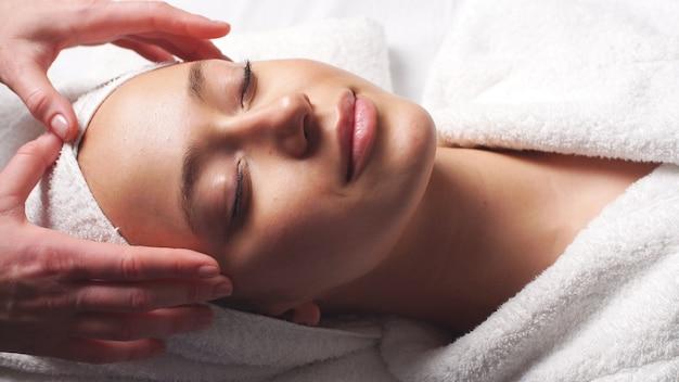 Спа массаж лица женщина. женщина, наслаждаясь расслабляющим массажем лица в косметологическом спа-центре.