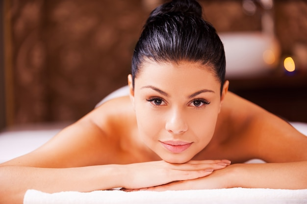 Spa woman. front view of beautiful young shirtless woman lying on massage table and looking at camera