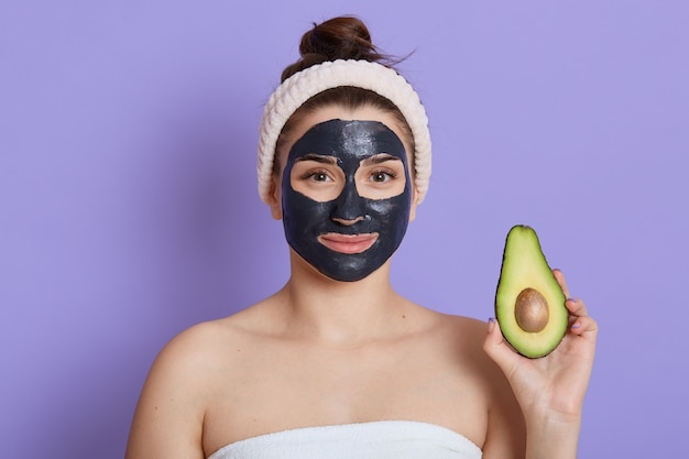 顔のマスクと手にアボカドの半分のスパの女性