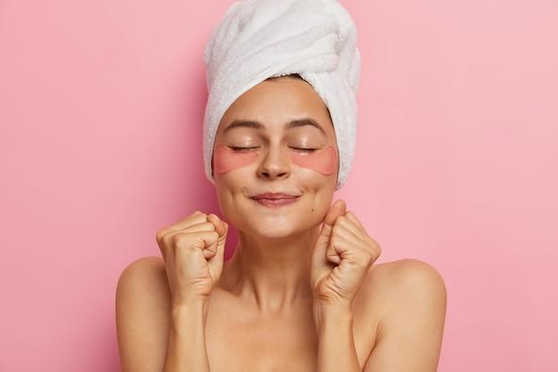 La donna della stazione termale fa una maschera per capelli, applica patch di idrogel, stringe i pugni come prevede per l'effetto del prodotto cosmetico, sta a torso nudo con gli occhi chiusi