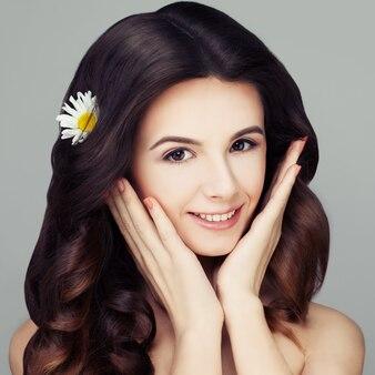 カモミールの花と健康な髪型の巻き毛のスパ女性