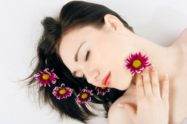 Спа молодая женщина с цветком хризантемы на сером