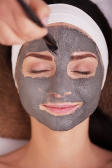 Spa . young woman with nutrient facial mask in beauty salon, close up