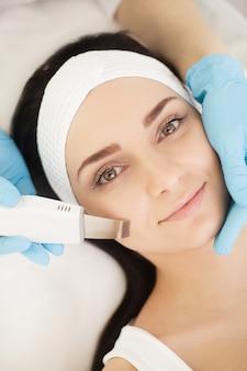 Омолаживающая процедура для лица. модель получает лифтинг-массаж в салоне красоты spa. пилинг, омоложение и гидратация. модель и доктор. косметология.