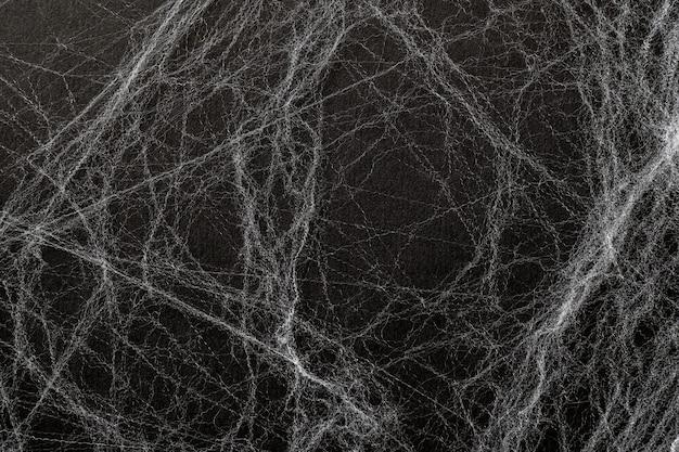 黒の背景に人工のクモの巣またはspaの巣。抽象的な背景。トップビュー、ハッピーハロウィン