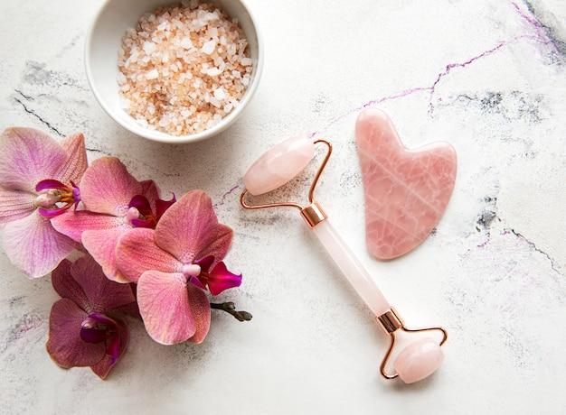 Набор натуральной органической косметики spa с цветами орхидеи. плоские лежал соль для ванн, лицо ролика, цветы орхидеи на фоне мрамора. уход за кожей, концепция косметического ухода