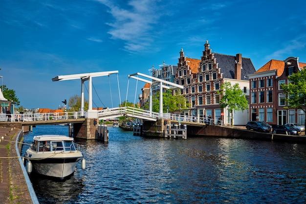 Spaarne river with boat and gravestenenbrug bridge in haarlem, n Premium Photo