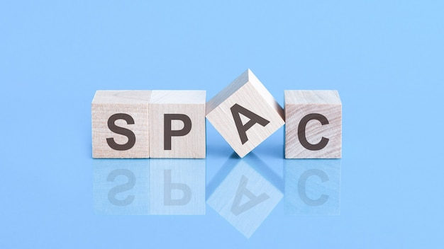 Spac symbol. wooden blocks with words 'spac, special purpose acquisition companies' on beautiful blue background, copy space. business concept.