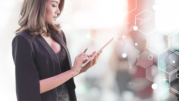 美しいセクシーなアジアのビジネスマンは、未来の技術の接続形状の背景とコピーspace.conceptビジネスミーティングのオフィススペースでタブレットを使用しています。