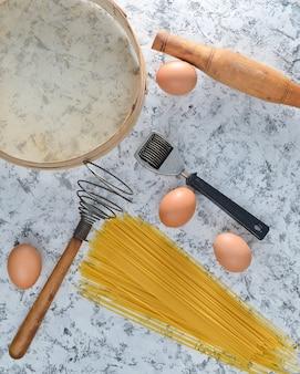 調理用のスペース。キッチンツールと白いコンクリートのテーブルで調理するための食材。パスタ、ふるい、泡立て器、麺棒、卵。上面図。