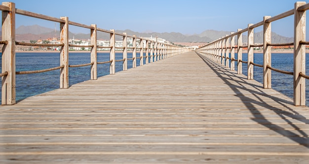 The space is a beautiful long wooden pier among the ocean and mountains.