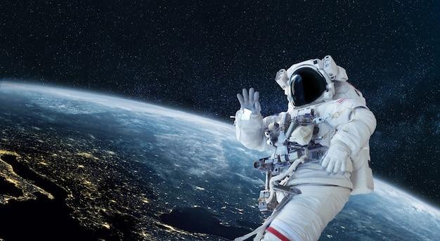 우주인 우주 비행사는 푸른 행성 지구의 배경에서 우주에서 인사하고 손을 흔듭니다. 우주 임무 벽지, 개념입니다. 우주에 오신 것을 환영합니다