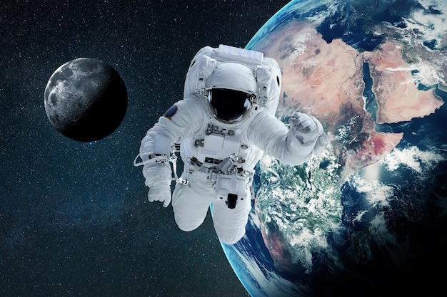 宇宙人は惑星地球と月とのオープンスペースで無重力で飛ぶ。宇宙と宇宙飛行士の壁紙
