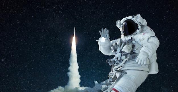 우주복과 모자를 쓴 우주인은 열린 공간을 여행하며 로켓 이륙 배경에 손을 흔듭니다. 우주선이 성공적으로 이륙합니다. 공간, 개념에 오신 것을 환영합니다