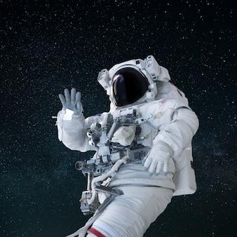 헬멧을 쓴 양복을 입은 우주인이 열린 공간에서 손을 흔들며 인사합니다. 안녕하세요 개념입니다. 우주 비행사 여행