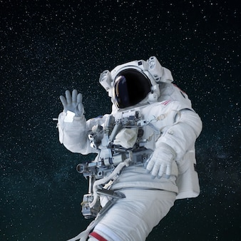 Space man in a suit with a helmet waves his hand and greeting in open space. hello concept. astronaut travels