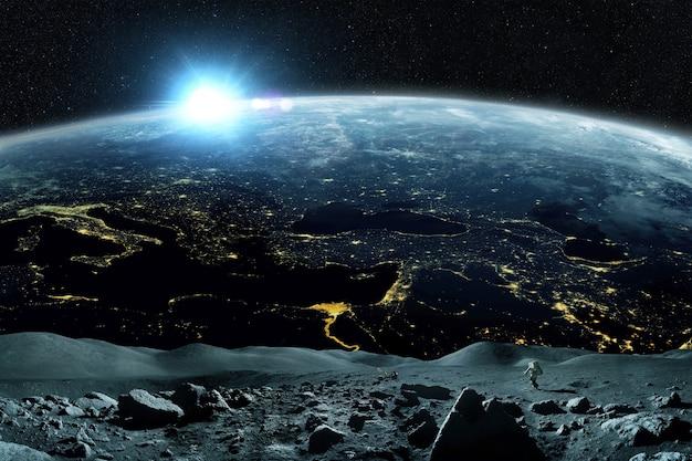 우주인은 놀라운 푸른 행성 지구와 수평선에 일몰과 함께 우주 공간의 달 위를 걷습니다. 우주 비행사 시작은 임무를 수행하고 위성 소행성을 탐험합니다.