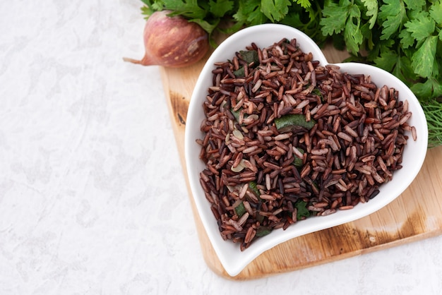 Space organic red rice in heart plate with vegetable food