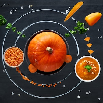 Space pumpkin solar system with orange vegetables, flat lay concept of healthy food background