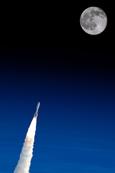 Nasaのイラストによって提供されたこの画像の月の要素に飛んでいる宇宙ロケット