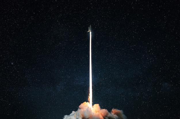 宇宙ロケットが星空に打ち上げられます。爆風と爆風を伴うスペースシャトルは、暗い背景の宇宙に持ち上げられます。成功したスタート、コンセプト