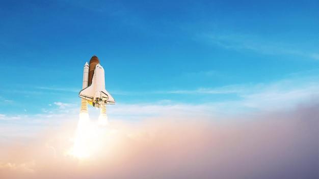 宇宙ロケットが青い空に浮かび上がります。雲の切れ間から宇宙船を打ち上げる