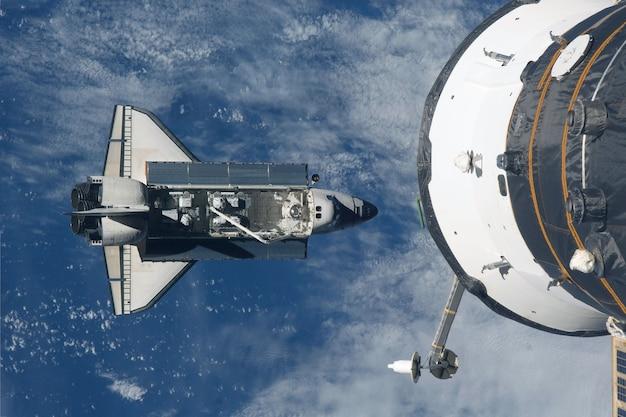 Космический шаттл летит под космической станцией. элементы этого изображения предоставлены наса.