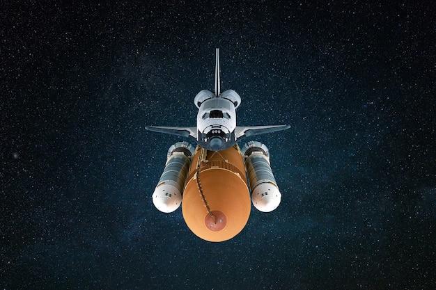スペースシャトルロケットは、星のある深宇宙を飛んでいます。宇宙船の正面図