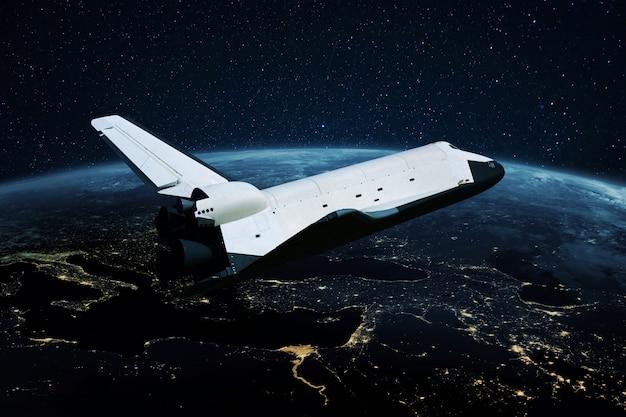 우주 왕복선 로켓은 메가시티의 밝은 불빛으로 밤 행성 지구 위의 열린 공간에서 날아갑니다. 우주선은 우주를 탐험합니다. 우주 임무 개념