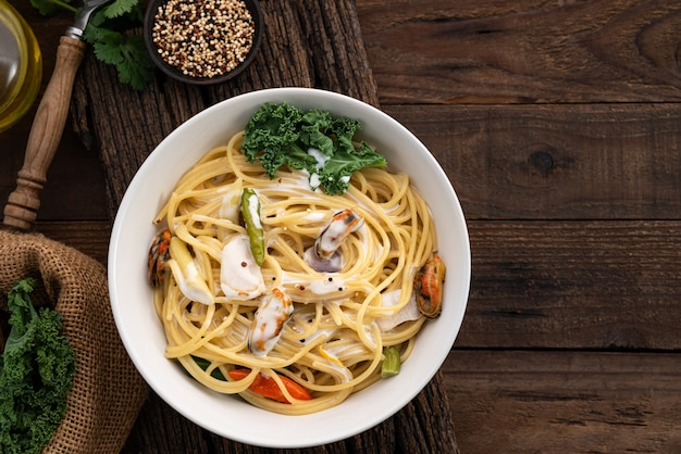 Space spaghetti cream sauce with mussels on wood