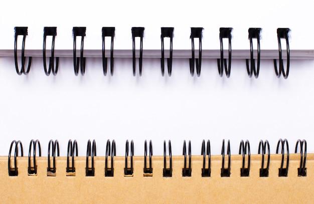 2つのスパイラルノートの間に白い紙にテキストを挿入するスペース。レンプレート。