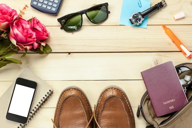 Верхний вид аксессуаров путешествия с паспортом, цветок, обувь, мобильный телефон, солнцезащитные очки, сумка, часы, записная книжка на столе деревянная с копией space.travel concept.
