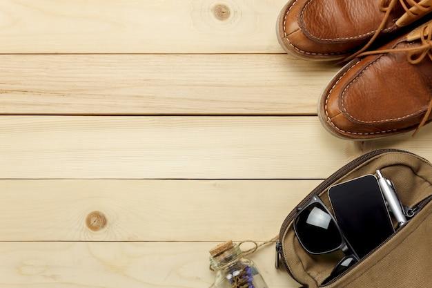 Верхний вид аксессуары путешествия с цветком, обувь, мобильный телефон, солнцезащитные очки, сумка на столе деревянные с копией space.travel концепции.
