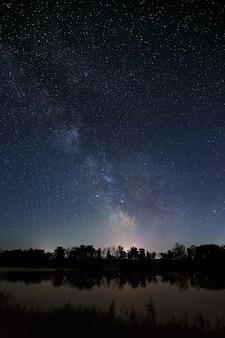 Космос со звездами в ночном небе. на длинной выдержке запечатлен пейзаж с рекой и деревьями.