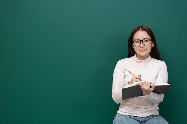 緑の壁の本を持つ宇宙女性