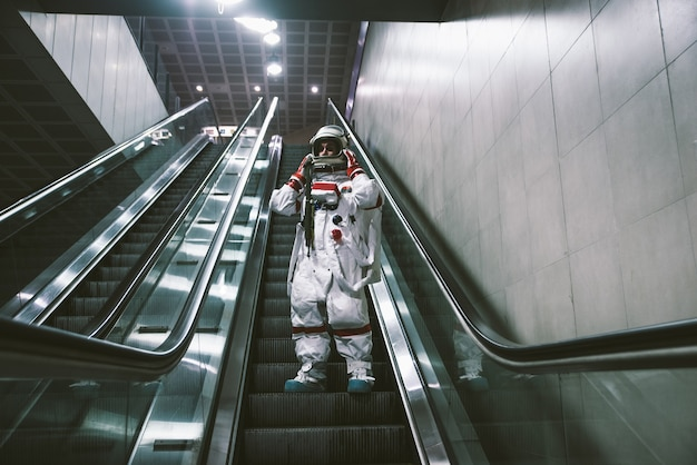Космонавт на футуристической станции. человек в скафандре уходит на работу и садится на поезд