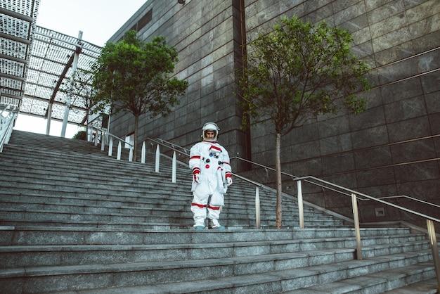 Космонавт в футуристической станции человек в скафандре гуляет по городу
