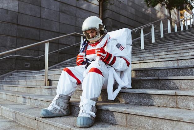 未来の駅にいる宇宙飛行士。都市部を歩く宇宙服を持つ男