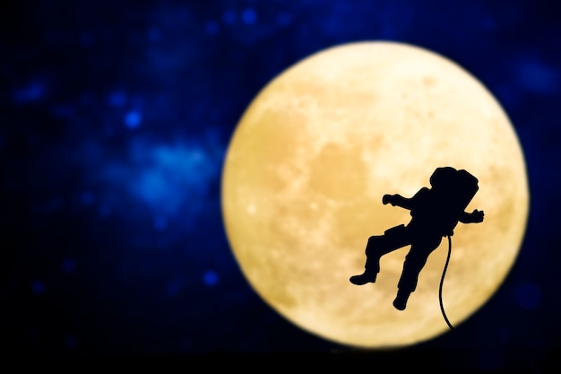 Spaceman silhouette over a full moon